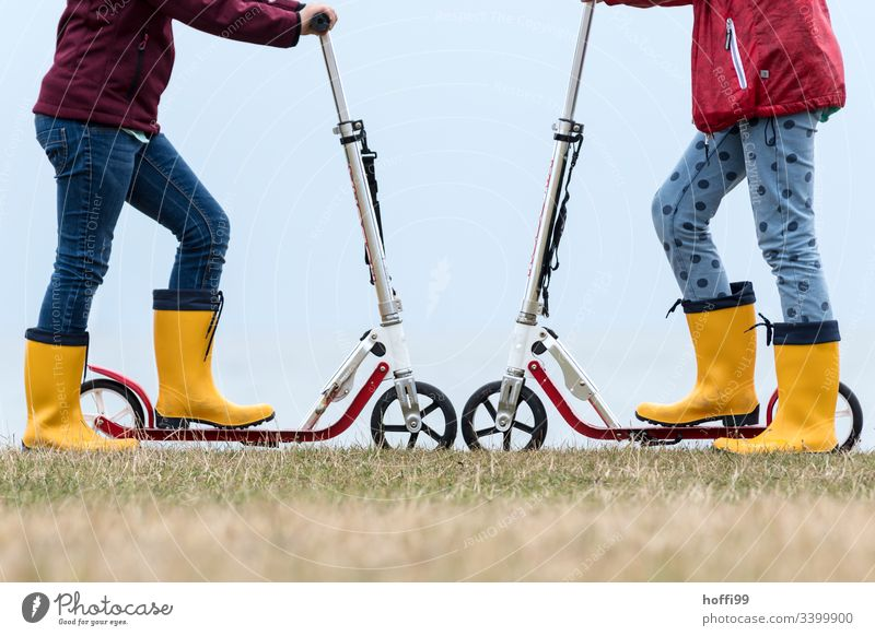 Scooter wheel to wheel with yellow rubber boots scooter Rubber boots Yellow Playing children Toys Playground Duel