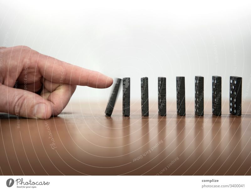Stone of the kick-off - knocking over dominoes Chain reaction Domino Dominos stop Stop Quit Infection Hold lasting Hand Reaction Business Career resolution
