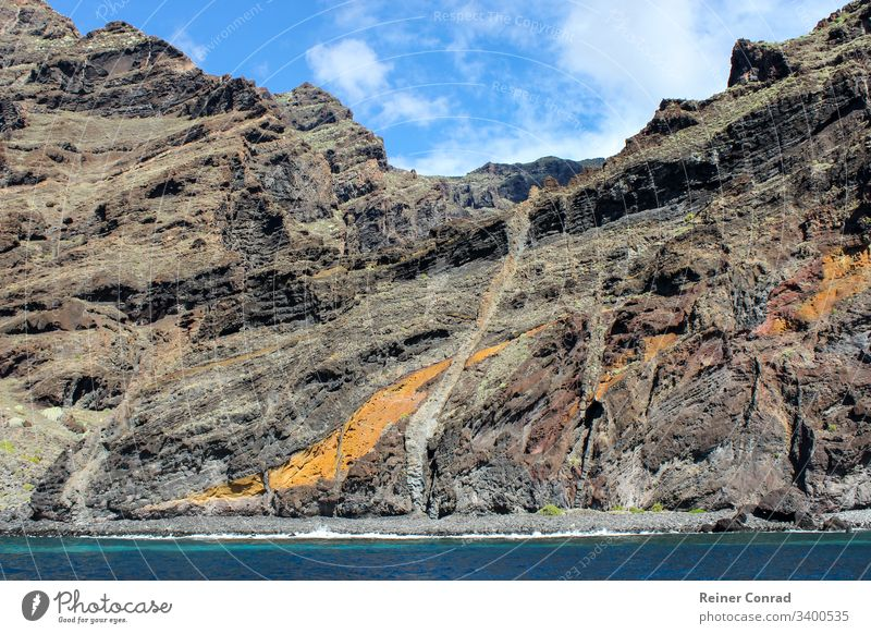 View on the steep coast of Los Gigantes on canary island tenerife with rocks in different colors canary islands los gigantes spain mountain range background