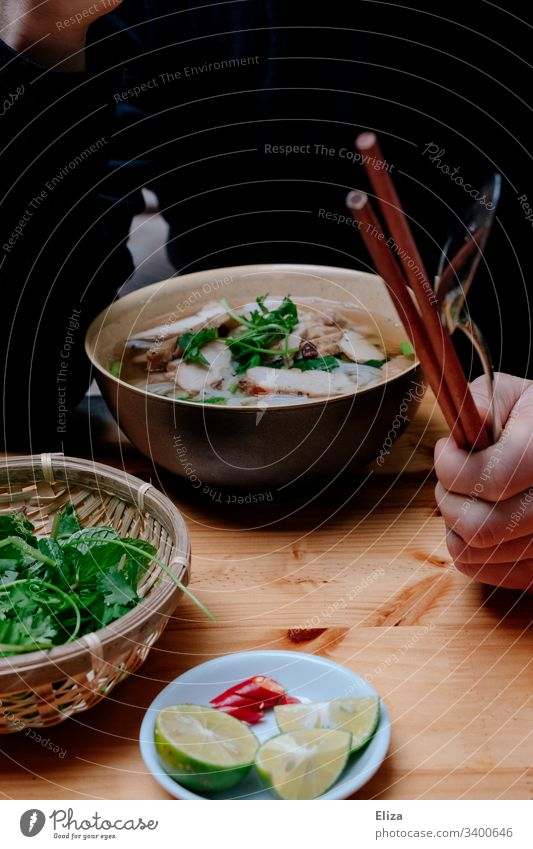 A bowl of Vietnamese Pho soup with fresh herbs and a person with chopsticks in his hand while eating Soup Pho Bo Fresh salubriously vacation Eating Hot limes