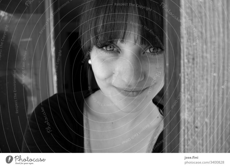 Young woman with bangs, looks into the camera and smiles fringe hairstyle Smiling kind Open Looking Black & white photo Looking into the camera pretty Feminine