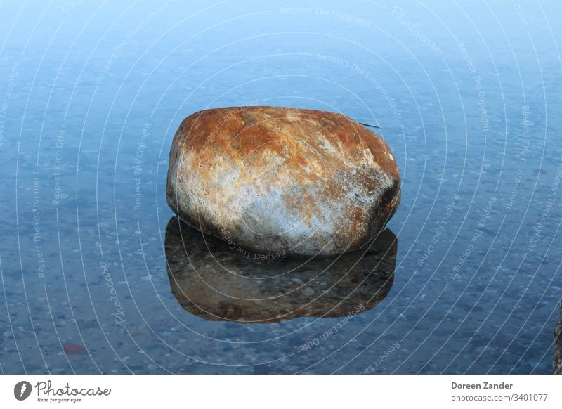 The lonely stone in the water Stone Water Lake Sky Nature Blue Clouds Deserted Background picture Rock Ocean Exterior shot Landscape Colour photo Coast