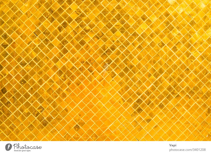 Closeup view of many gold shiny squares surface texture abstract background pattern mosaic design wallpaper backdrop color interior modern tile golden