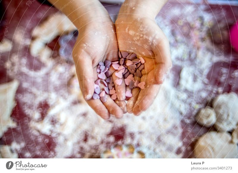 Child little hands holding heart shaped sweets child hearts Heart-shaped Love Colour photo pink purple cooking baking flour fingers desert Close-up