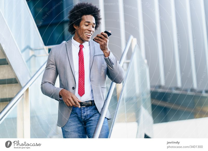 Black Businessman using a smartphone near an office building black businessman curly afro you hair suit african male adult portrait american person device