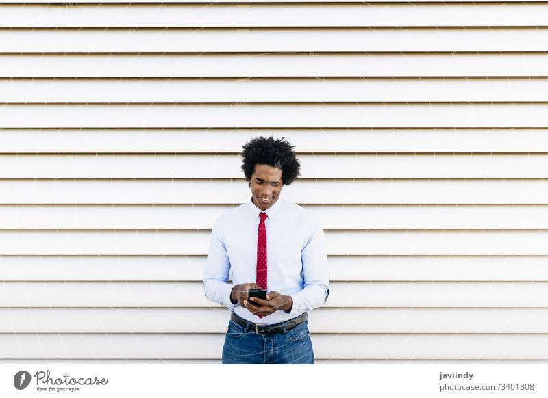 Black Businessman using a smartphone with a white blinds background black businessman curly afro you hair suit african male adult portrait american person