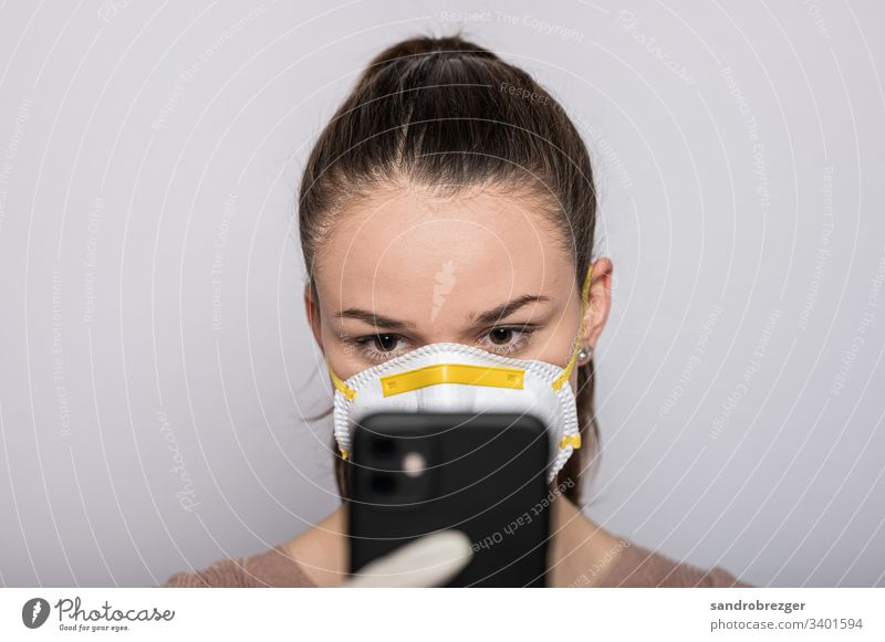 Woman with a mouthguard and disposable gloves types on her mobile coronavirus covid-19 Virus Illness pandemic Epidemic Mask guard sb./sth. hand protection