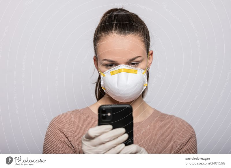 Woman with mouthguard and disposable gloves reads on smartphone coronavirus covid-19 Virus Illness pandemic Epidemic Mask guard sb./sth. hand protection Sterile