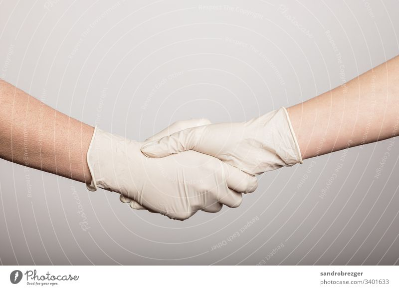 Handshake in times of the Corona Virus coronavirus covid-19 Illness pandemic Epidemic Mask guard sb./sth. disposable gloves hand protection Sterile Sick