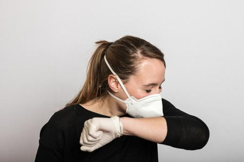 Woman with mouthguard and disposable gloves sneezes into the crook of her arm coronavirus covid-19 Virus Illness pandemic Epidemic Mask guard sb./sth.