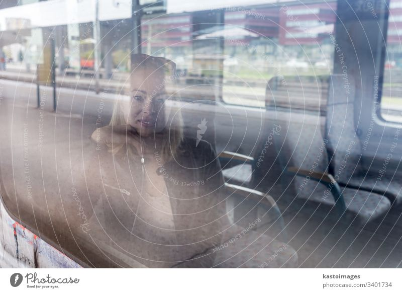 Young woman traveling by train, looking out window while sitting in train. girl young female passenger ride railway adult journey person transport
