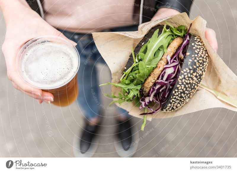 Female Hands Holding Delicious Organic Salmon Vegetarian Burger and Homebrewed IPA Beer. burger beer hands letuce eating salmon organic meat unhealthy woman
