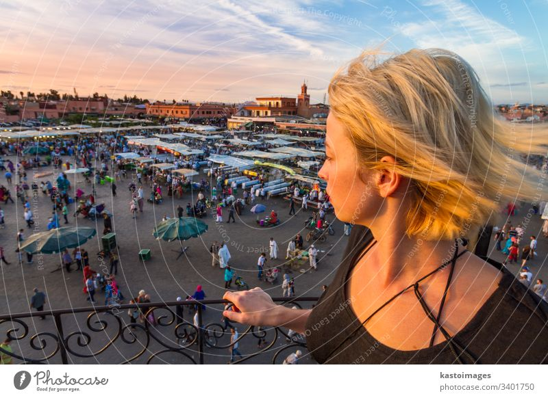 Woman overlooking Jamaa el Fna market square in sunset, Marrakesh, Morocco, north Africa. marrakesh morocco traveler tourist woman lady marrakech africa jamaa