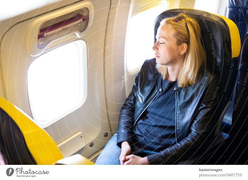 Tired blonde casual caucasian lady napping on seat while traveling by airplane. sleep woman flight business economy stress trip airline window space confortable