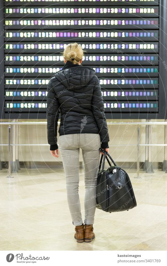 Female traveller checking a departures board at the airport terminal hall. display information schedule trip woman airline arrival baggage flight girl luggage