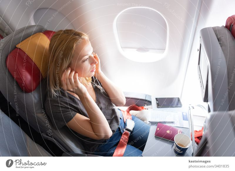 Woman flying on commercial passengers airplane, listening to music. flight travel woman young aircraft female cabin caucasian entertainment headphones cup
