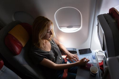 Casual woman flying on commercial passengers airplane, filling in immigration form. flight travel cabin female music young aircraft entertainment headphones cup