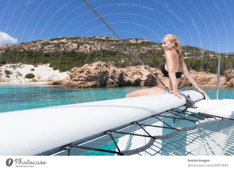 Woman relaxing on a summer sailing cruise, sitting on a luxury catamaran near picture perfect white sandy beach on Spargi island in Maddalena Archipelago, Sardinia, Italy.