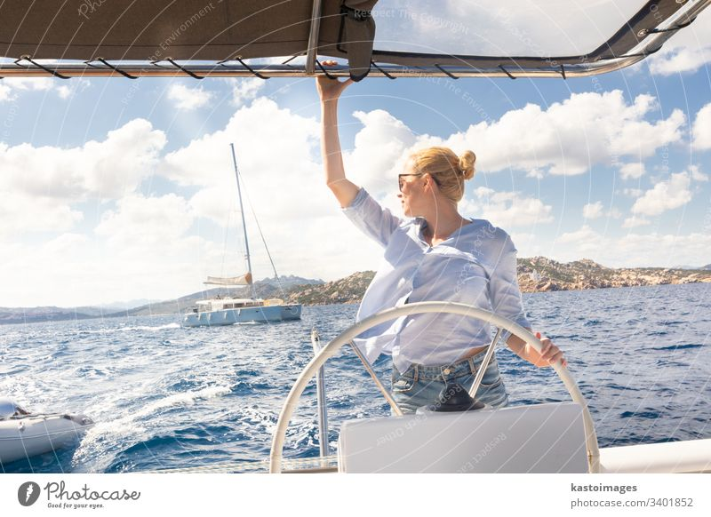 Attractive blond female skipper navigating the fancy catamaran sailboat on sunny summer day on calm blue sea water. nautical steering wheel sailing boat woman