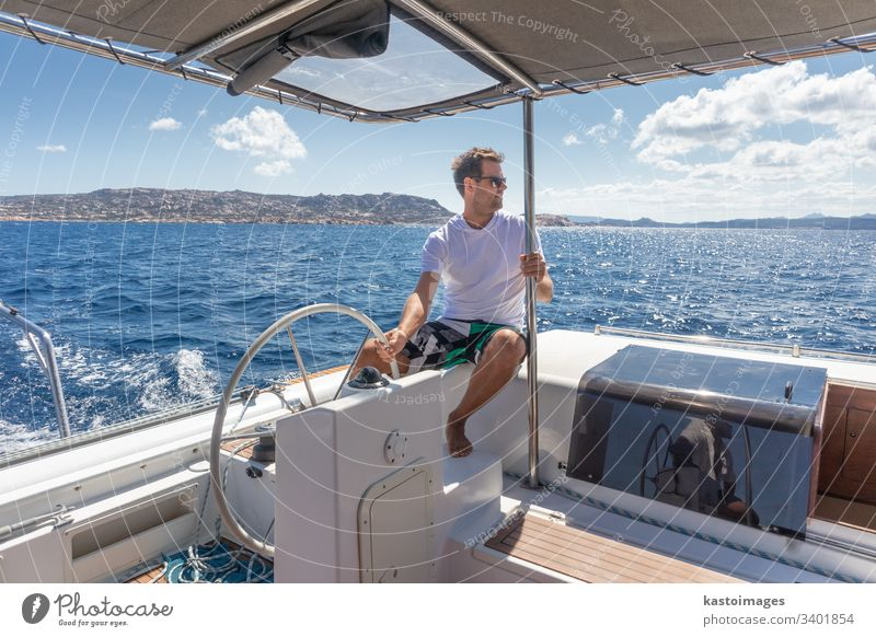 Attractive male skipper navigating the fancy catamaran sailboat on sunny summer day on calm blue sea water. nautical steering wheel sailing boat ocean ship
