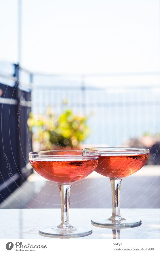 Two crystal stemmed glasses with rose wine outdoors on marble table. Aperitif time white party pink drink dinner luxury light background modern alcohol bar