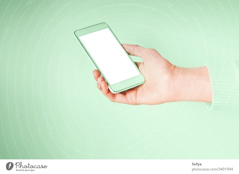 Hand with mobile phone and empty white screen on mint green color 2020 green mint neo using color year hands smartphone woman device internet connection