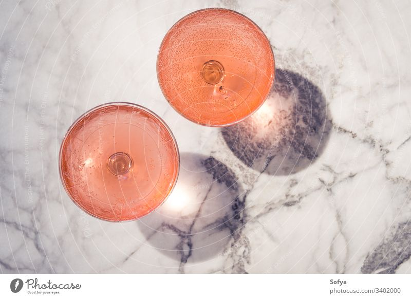 Two crystal stemmed glasses with rose wine outdoors on marble table in hard light producing shadows white party pink drink dinner luxury background modern