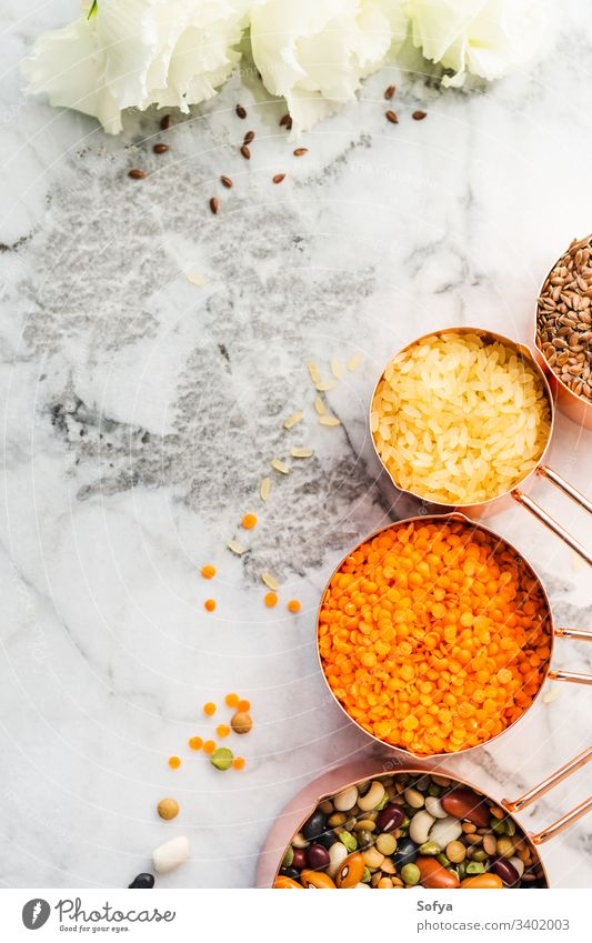 Copper cups with beans and cereal and white flowers on marble table measuring zero waste food flat lay vegan kitchen meal prep bulk lentils copper cooking