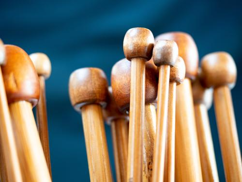 wooden knitting needles Blockheads Group symbol Knit Detail Close-up shallow depth of field warm colors Brown tones dark blue Copy Space top Leisure and hobbies