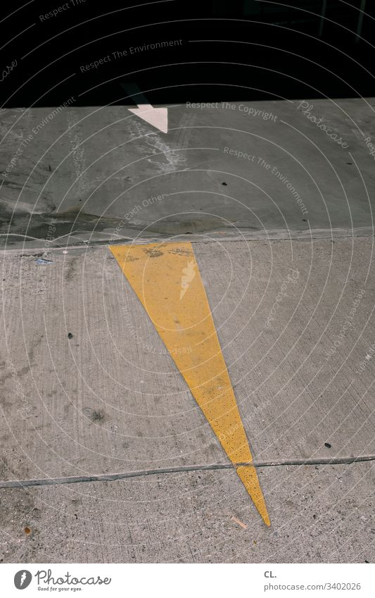 two arrows on the floor Arrow Ground Direction Trend-setting Orientation Yellow Gray Right ahead Colour photo Sign Deserted Signs and labeling Exterior shot