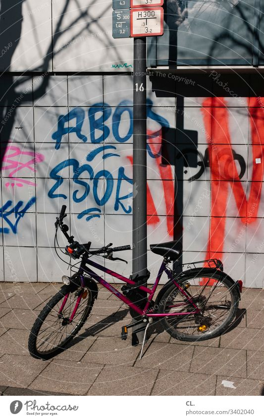 a bicycle is on the sidewalk off Graffiti Dirty Bicycle Wall (building) Traffic infrastructure Colour photo Exterior shot Deserted Lanes & trails Transport