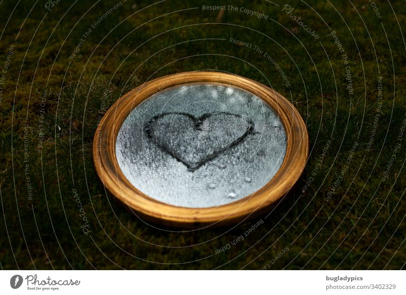 Golden Mirror lies in a meadow. There are drops of water on the mirror. A heart is painted on the mirror surface. golden Meadow Moss Nature Drops of water