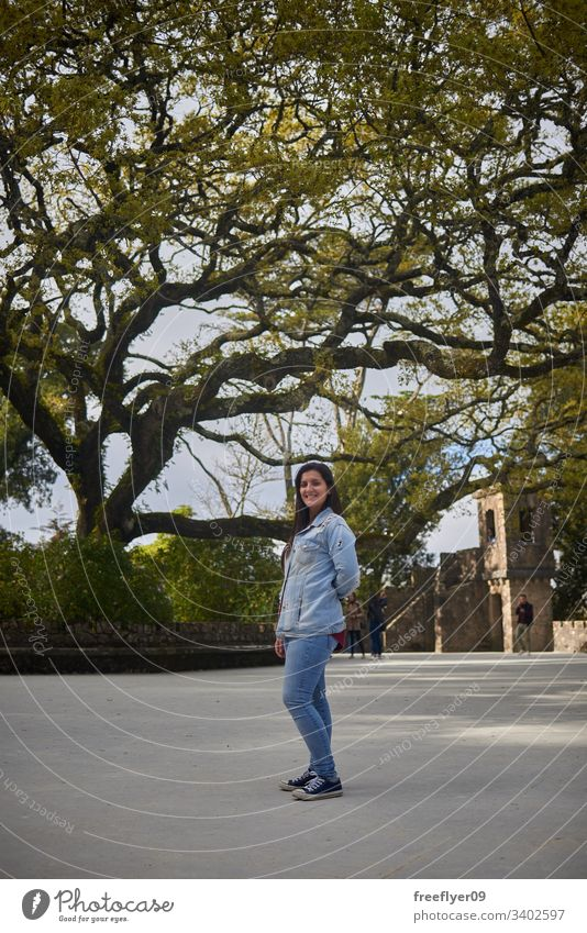 Young woman on Regaleira, Sintra, Portugal young tree tourism tourist forest park famous historic nature path landscape hiking hike grass palace art europa red