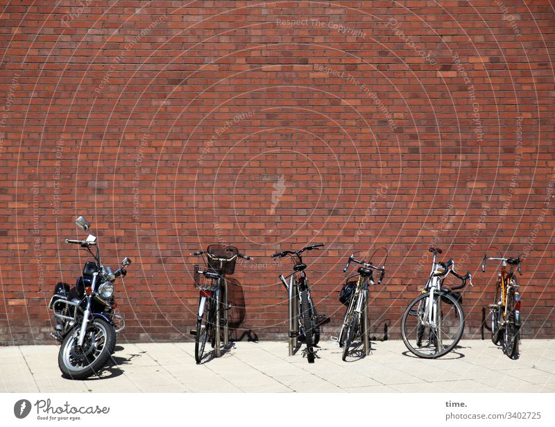Parking space management ::: five bicycles and a power bolt basking in the sun on a boring red brick wall Brick wall Bicycle Parking lot Motorcycle sunny