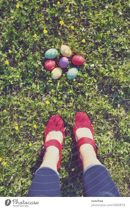 woman stands on the grass in front of colorful easter eggs Woman Stand Legs feet High heels Red variegated Easter Easter eggs colored Footwear colorful eggs