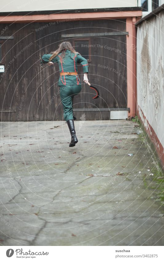 teenager in uniform jumps over in the courtyard with a sickle in his hand Girl Young woman Youth (Young adults) Puberty Uniform Suit Hammer Tool Wooden gate