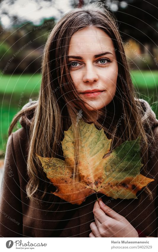 Beautiful girl holding a leaf with autumn colors moody woman portret brown clothed expresion face beauty nature fashion 20s