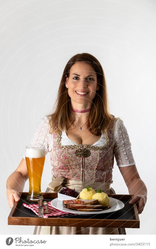 Woman in a Bavarian Dirndl with tray Dinner stop White segregated Oktoberfest Roast pork serve Carrying Alcoholic drinks Waitress Tray Costume Wheat beer