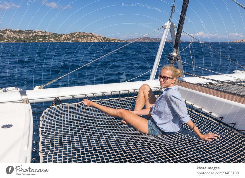 Woman relaxing on a summer sailin cruise, sitting on a luxury catamaran, sailing in Maddalena Archipelago, Sardinia, Italy. woman boat sea sailingboat nautic