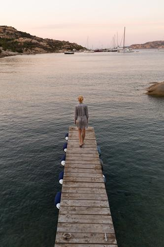Beautiful woman in luxury summer dress standing on wooden pier enjoying peaceful seascape at dusk. Female traveler stands on a wooden pier in Porto Rafael, Costa Smeralda, Sardinia, Italy.