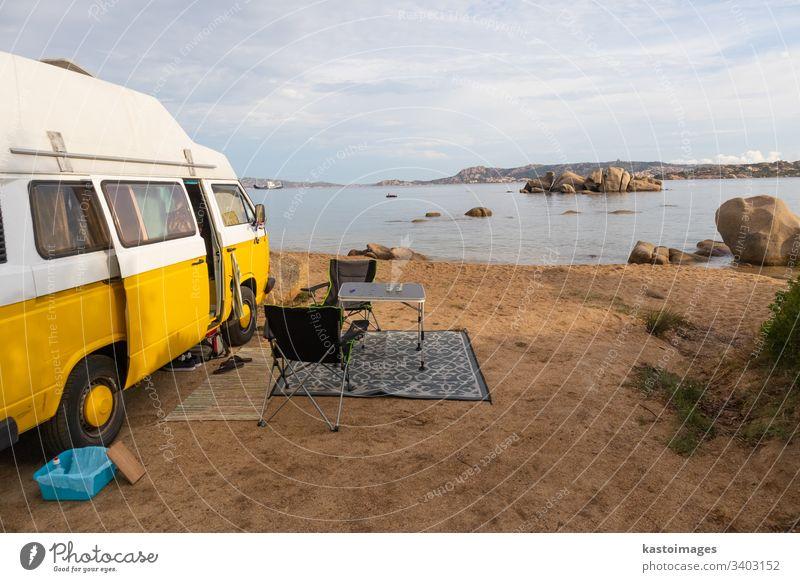 Vintage minivan car on camping spot on beach on Sardinia island, Italy. retro hippie vintage road trip travel camper adventure holiday lifestyle vacations