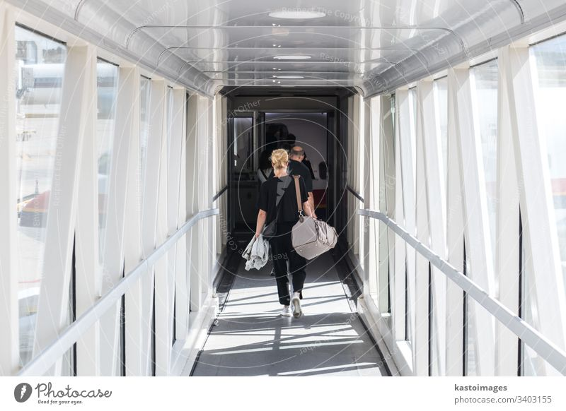 Female passenger carrying the hand luggage bag, walking the airplane boarding corridor. travel aircraft woman transfer transport traveller holiday airport