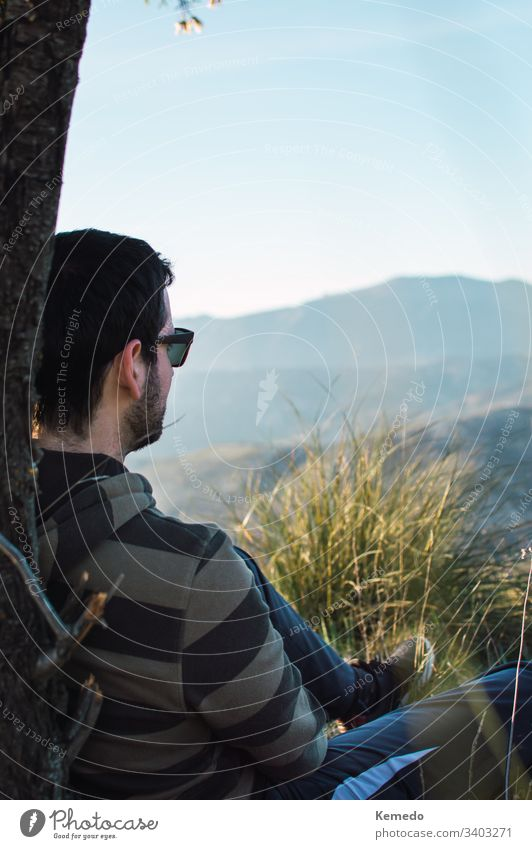 Side view of guy in sunglasses sitting on grass near tree trunk on sunny day with the mountains in the background. nature Thoughtful young repose away look end