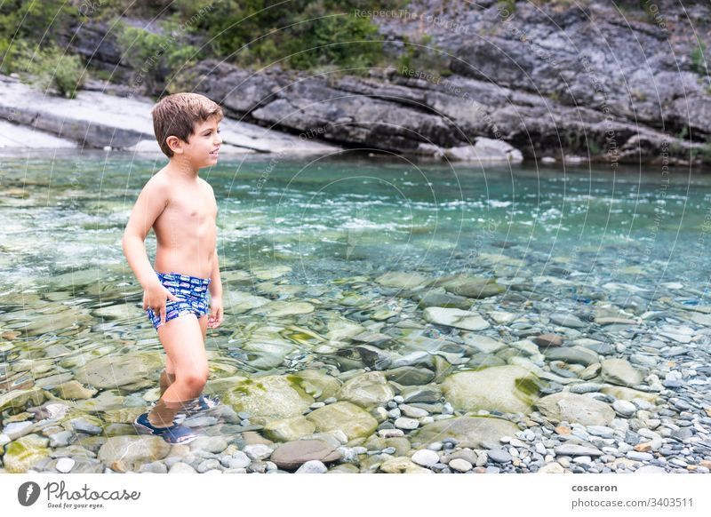 Little child in the middle of a wild river activity alone cheerful childhood cinca coast crossing day enjoyment flow fun game girl happiness healthy holidays