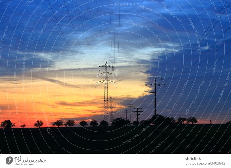 Power line in evening sun stream mast high voltage High voltage Energy Electricity Technology Cable Energy industry Sky Colour photo Electricity pylon