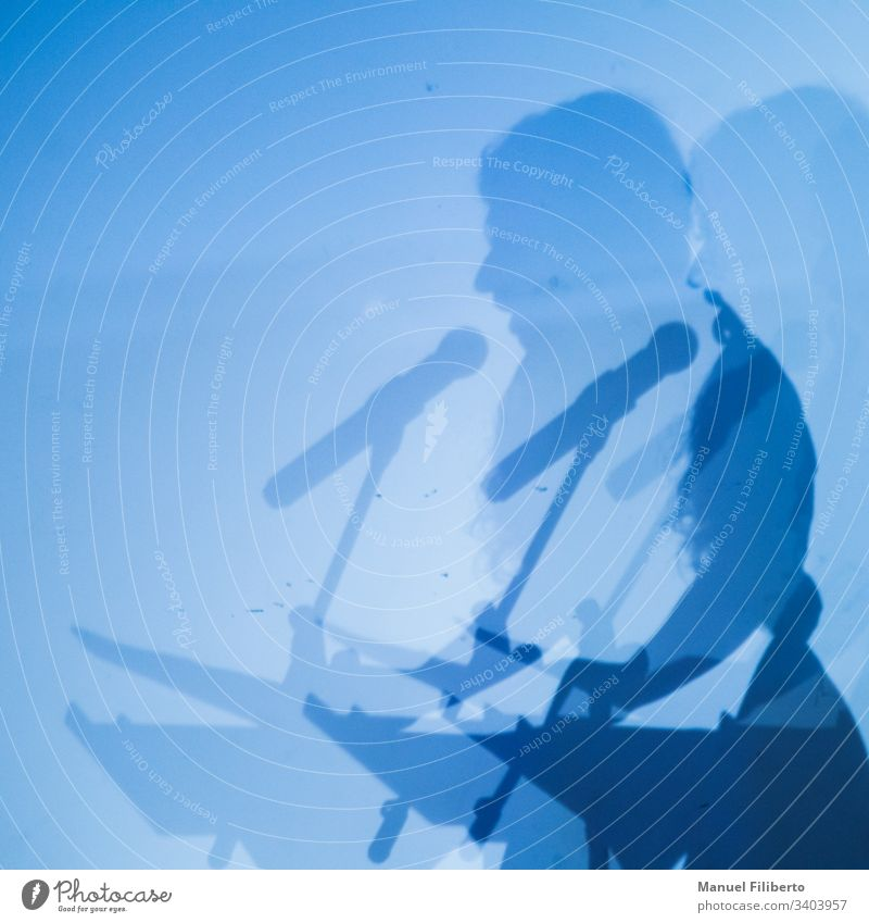 Double shadow of a person speaking through a microphone on a blue wall speech concert silhouette male music party live meeting performance pop singer song