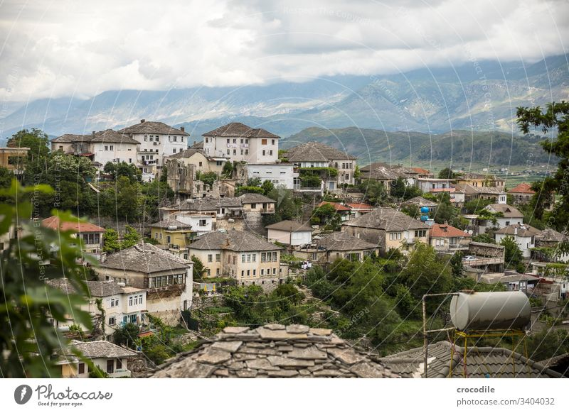 View of the old town of Gjirokaster, Albania Old town Historic Housefront Town Balkans Mountain UNESCO World Heritage Site Clouds roofs Water tank