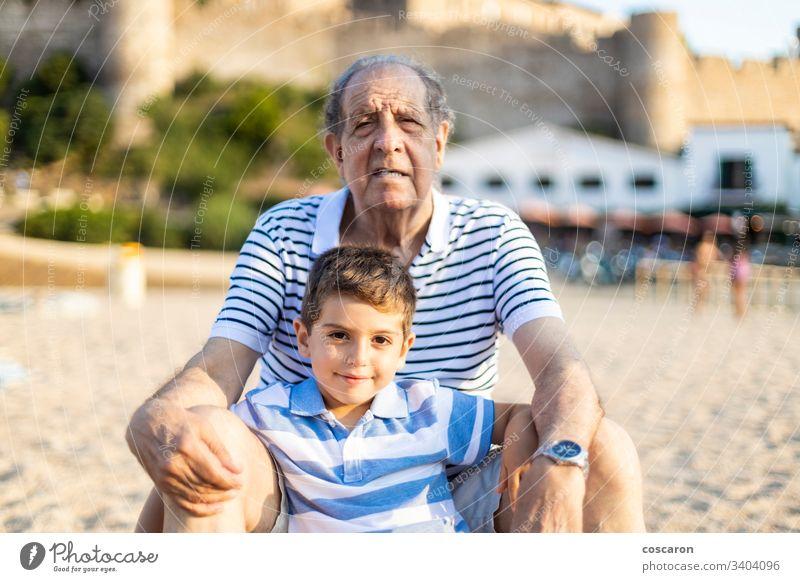 Portrait of grangfather and grandson on the beach boy caucasian cheerful child children coast enjoyment family fun girl grandchild grandchildren granddaughter