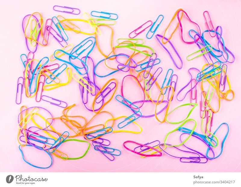 Colorful rubber bands on pink paper background stationery clip office color flat lay rubber ring girl style workspace supply study tool accessory school kid