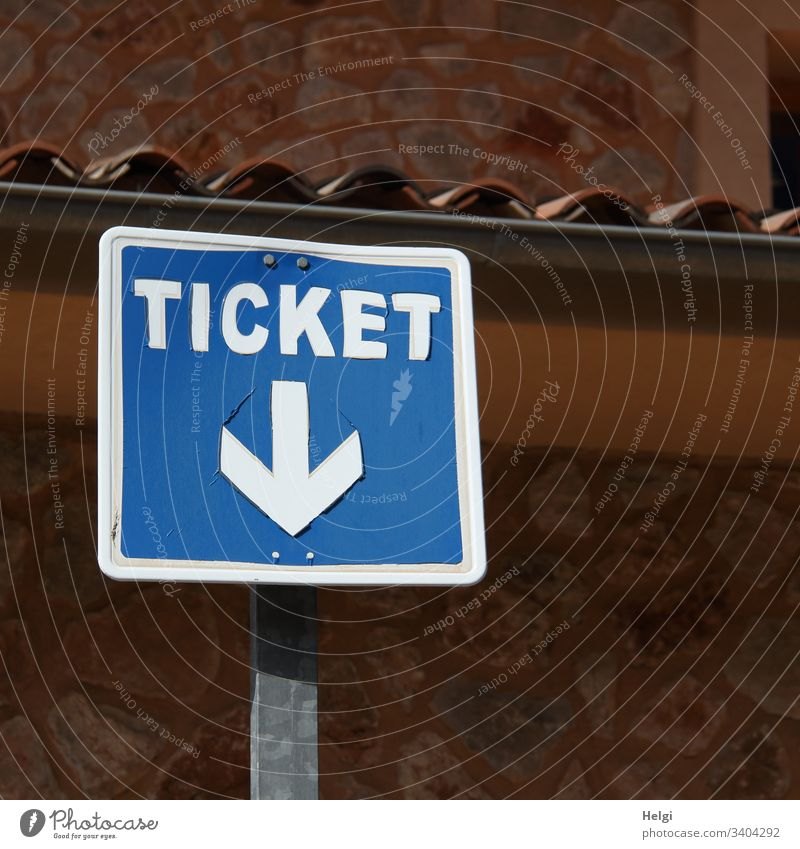 Ticket, sign with arrow pointing down in front of a wall Signage Signs and labeling Exterior shot Transport Blue White Wall (building) Brown Deserted square